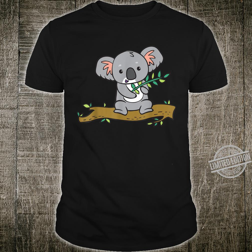 A koala bear with a branch of eucalyptus sits on a tree. Shirt