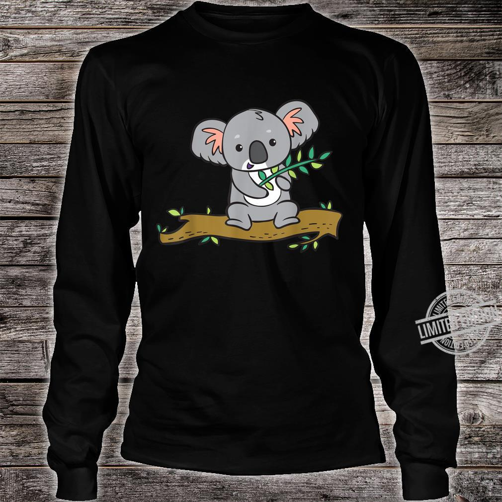 A koala bear with a branch of eucalyptus sits on a tree. Shirt long sleeved