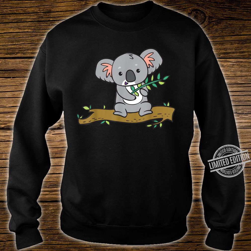 A koala bear with a branch of eucalyptus sits on a tree. Shirt sweater